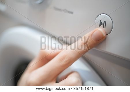 Girl's Hand Presses The Start, Pause Button On The Control Panel Of The Washing Machine Close-up