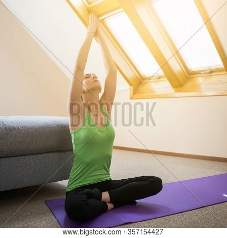 Young Woman Is Practicing Yoga At Home. Padmasana / Lotus Position