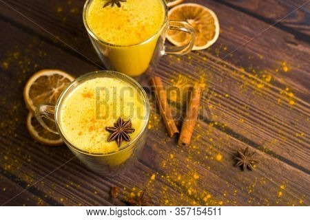 Golden Milk Drink With Turmeric And Honey On A Dark Wooden Background In Transparent Glasses For Hea