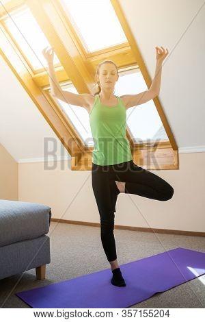 Young Woman Is Practicing Yoga At Home. Vrikshasana / Tree Pose