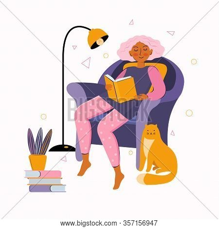 Young Woman Spends Time At Home Reading A Book. Literary Fan Reading Books While Sitting In A Chair.
