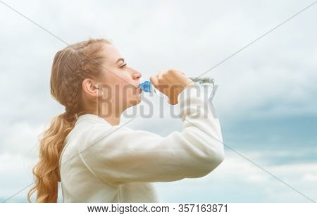 A Young Woman Drinks Water From A Plastic Bottle. The Girl Quenches Her Thirst After Running.