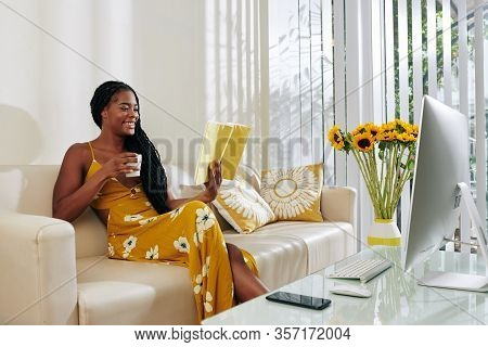 Beautiful Smiling Young Woman Drinking Cup Of Delicious Coffee And Reading Book When Staying At Home