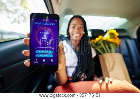 Woman Using Smart Charger And Checking Battery Status Via Application On Smartphone When Riding In C