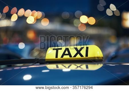Lighting Taxi Sign On Roof Of Car On City Street At Night.