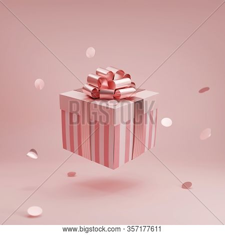 Pink Gift Box With Golden Ribbon Bow Levitating On Pastel Pink Background. Flying Stripped Present W