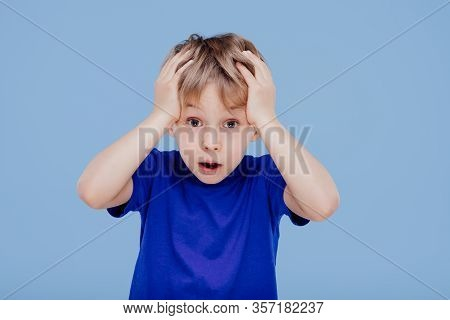 Astonished Little Boy With Hands On Head Looks At Camera Dressed In Blue T-shirt, Isolated On Blue B