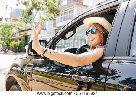 Beautyiful Smiling Young Woman In Hat And Sunglasses Looking Out Of Car Window And Waving With Hand