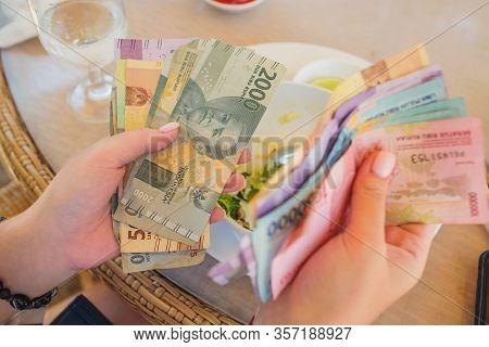 Hand Holding Money In Indonesian Rupiah After Get Thr Tunjangan Hari Raya Which Is Eid Mubarak Bonus