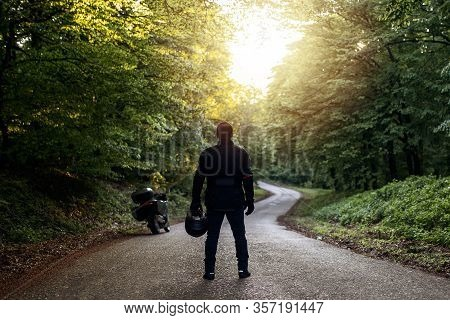 Motorcycle Guy In Raiders Clothes, Gearing Up. A Young Men Stands Near An Motorcycle In Nature Durin