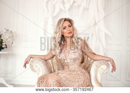 Amazing Luxury Elegant Woman In Stylish Golden Party Dress Sitting On Modern Armchair Before White F