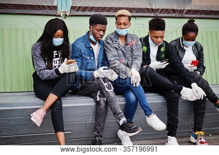 Group Of African Teenagers Friends Sitting With Phones, Wearing Medical Masks Protect From Infection