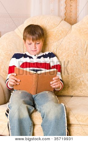 boy reads book on sofa