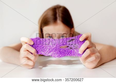 A Beautiful Girl Stretches The Purple Slime To The Sides And Hides Behind It. Children's Hands Play