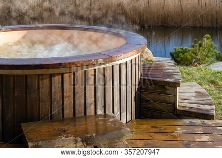 How Water Swirling In Wooden Hot Tub Outside In Nature. Enjoying Hot Steaming Pool On A Sunny Day, P