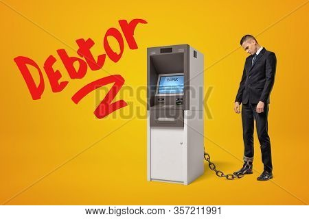 Sad Young Businessman Standing In Half-turn Chained To Atm On Amber Background With Big Red Title De