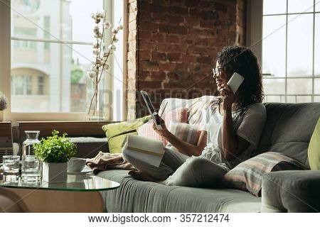 Talking On Phone. Woman, Freelancer During The Work In Home Office While Quarantine. Young Female Bu