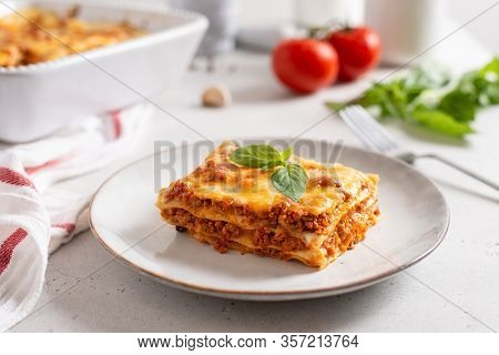 Piece Of Tasty Hot Lasagna Served With A Basil Leaf On A Gray Plate. Italian Cuisine, Menu, Recipe.