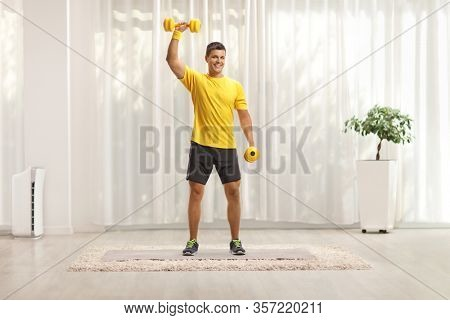 Full length portrait of a man exercising with weigths at home