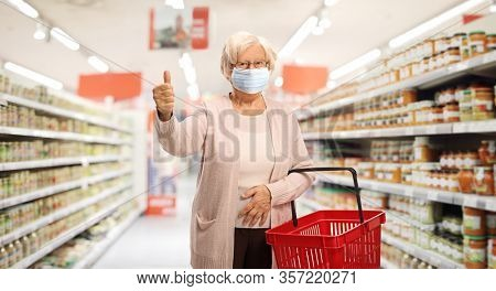 Elderly woman shopping in a supermarket with a protective face mask and showing thumbs up