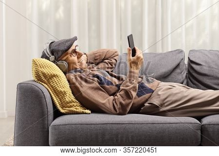 Elderly man on a sofa holding a mobile phone and listening to music on headphones at home