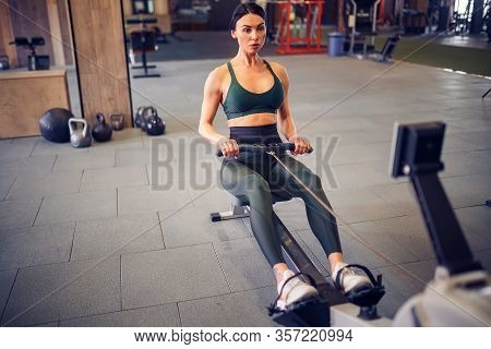Determined Young Woman Working Out On Row Machine In Fitness Studio.
