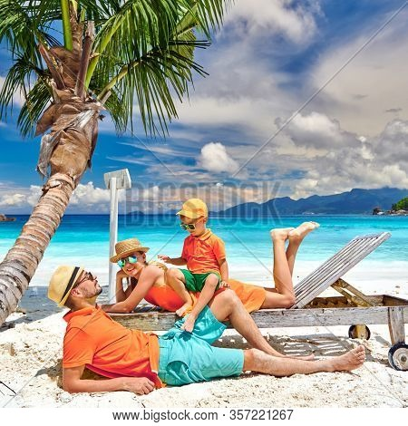 Family on beautiful Petite Anse beach, young couple with three year old toddler boy. Summer vacation at Seychelles, Mahe.