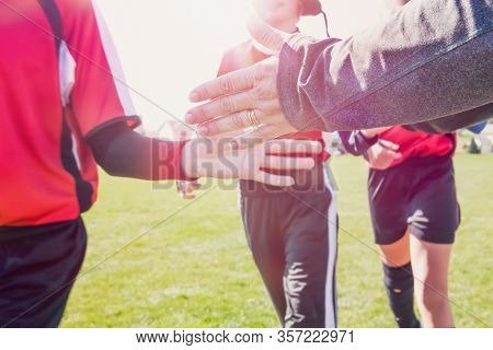 High Five line after a childs soccer game toned image, focus on adult hand
