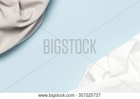 White And Gray Crumpled Natural Cotton Fabric On Delicate Blue Background Top View Flat Lay With Cop