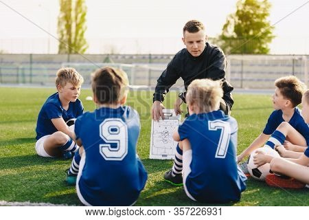 Young Coach Teaching Kids On Football Field. Football Coach Coaching Children. Soccer Football Train