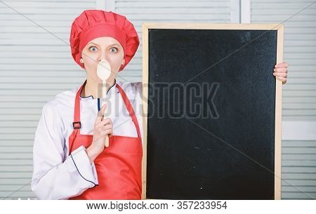 A Training School For Cooks. Pretty Woman Holding Spoon At Empty Blackboard. Culinary Education In C