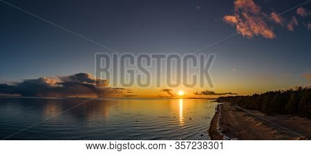 Drons Flight Over The Coast At Sunset, The Picturesque Sunset, Quiet Water, A Sandy Beach, Tops Of T