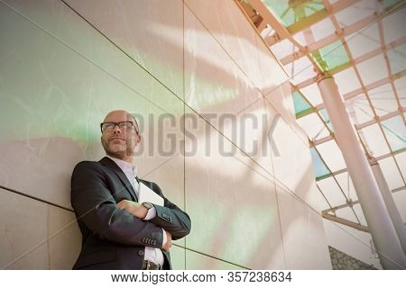 Portrait of businessman standing with arms crossed while leaning on wall