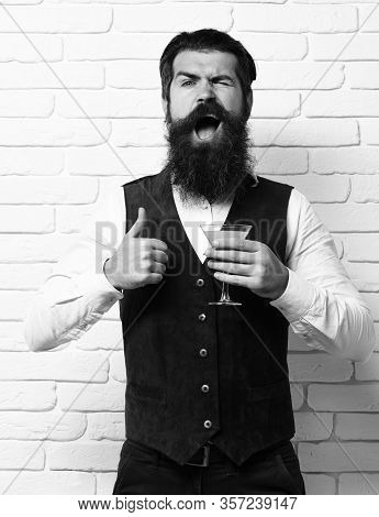 Handsome Bearded Man With Long Beard And Mustache Has Stylish Hair On Funny Face Holding Glass Of Al