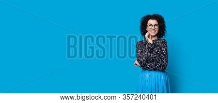 Cheerful Caucasian Lady With Curly Hair Smiling While Touching Her Chin On A Blue Background With Fr