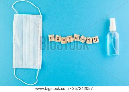 The Inscription Covid-19 Laid Out Of Wooden Cubes On A Blue Background. Medical Concept For Health A