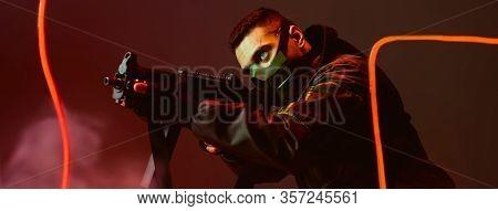 Panoramic Shot Of Bi-racial Cyberpunk Player In Protective Mask Aiming Gun Near Neon Lighting On Bla