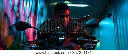 Panoramic Shot Of Bi-racial Cyberpunk Player On Motorcycle Aiming Gun On Street With Graffiti
