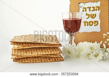 Pesah Celebration Concept - Jewish Passover. Background With White Flowers, A Glass Of Wine, Matzoh