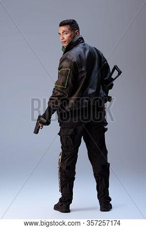 Mixed Race Cyberpunk Player Holding Gun And Standing On Grey