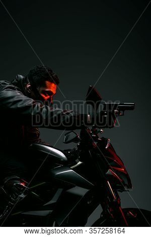Side View Of Armed Bi-racial Cyberpunk Player In Mask Riding Motorcycle And Holding Gun On Grey