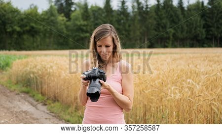 Young Female Photographer Checking Setting On Her Digital Camera As She Is Standing Outside By A Bea