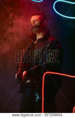 Bi-racial Cyberpunk Player In Protective Mask Holding Gun Near Neon Lighting On Black With Smoke