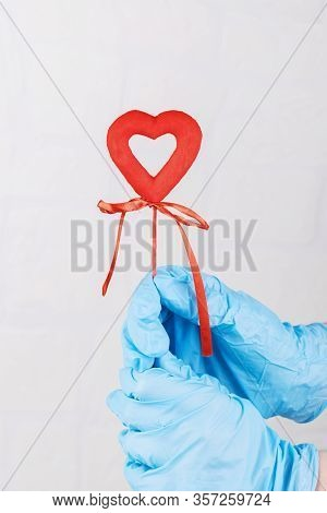 Female Hand In Blue Medical Gloves Holding A Red Heart, Symbol Of Life. Concept Support Of People In