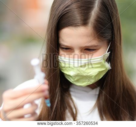 Hand Of Young Nurse Wears Surgical Mask Checks Blood Sample For Analysis In Hospital Laboratory