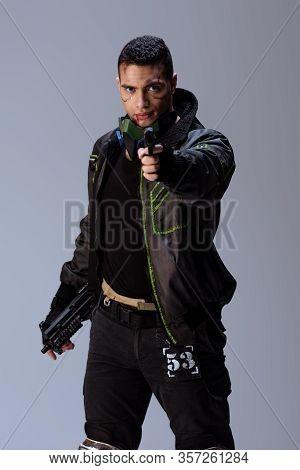Handsome Bi-racial Cyberpunk Player Aiming Gun Isolated On Grey