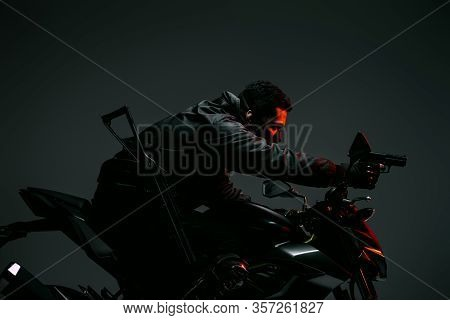 Profile Of Armed Bi-racial Cyberpunk Player In Mask Riding Motorcycle And Holding Gun On Grey