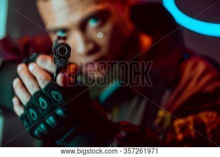 Selective Focus Of Gun In Hands Of Armed Bi-racial Cyberpunk Player