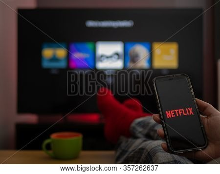 Uk, March 2020: Tv Television Netflix On Phone And Tv With Feet Up Comfy