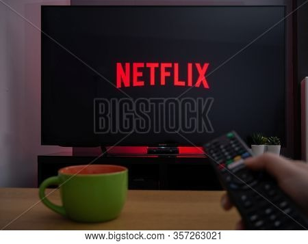 Uk, March 2020: Tv Television Netflix Logo On Screen With Remote